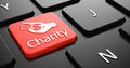 Charity on red keyboard button with money in the hand icon black computer Royalty Free Stock Photography