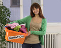 Charity: Woman with clothing donation box Stock Images