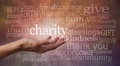 Charity word wall banner woman s outstretched open hand with the in white above palm surrounded by related words on a rustic Royalty Free Stock Photo