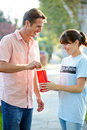 Charity worker collecting from man in street smiling Stock Photo