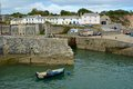 Charlestown harbour in cornwall england entrance with people walking and sitting Royalty Free Stock Photo