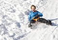 Charlie sledge cute young boy laughing as he is sledging downhill in the snow Stock Photos
