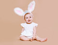 Charming baby sitting in costume easter bunny on a background Stock Photography