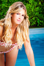 Charming blonde girl in swimsuit bikini. Pool Royalty Free Stock Photo