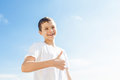 Charming boy with thumbs up standing outside against blue sky Stock Image
