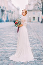 Charming bride in long lace dress holding vintage bouquet looking over shoulder into the camera with old city Royalty Free Stock Photo
