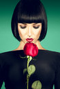 Charming brunette with der rose on green background in studio Royalty Free Stock Images