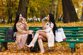 Charming brunette girlfriends drinking coffee sitting on bench in the park Royalty Free Stock Photo