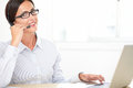 Charming callcenter employee working on desk with glasses the while smiling and looking at you Stock Image