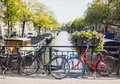 Charming canal with boat houses and bicycles in Amsterdam old town, Netherlands. Popular travel destination and tourist attraction Royalty Free Stock Photo
