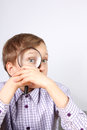 Charming caucasian boy purple shirt looking magnifying glass grimacing Royalty Free Stock Photos
