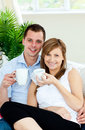 Charming couple holding cups of coffee smiling Stock Images