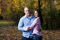 Charming couple standing together at the park happy in woods during autumn Royalty Free Stock Images