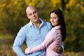 Charming couple standing together at the park happy in woods during autumn Stock Photos