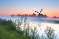 Charming dutch windmill by river at sunrise Stock Images