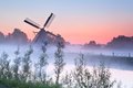 Charming dutch windmill at sunrise in fog Royalty Free Stock Photo