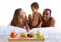 Charming family having breakfast in parents bed at home concept of cheerful american Royalty Free Stock Image