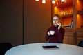 Charming female having mobile phone conversation in cafe while sitting against background with copy space area for text young Stock Images