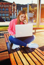 Charming female teenager sitting on park bench  with laptop Royalty Free Stock Photo