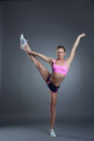 Charming flexible athlete doing vertical split on gray background Royalty Free Stock Images