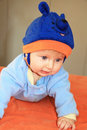 The charming four months boy with blue eyes in a blue hat with ears tries to creep Stock Photos