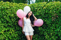 Charming girl with balloons in green hedgerow outdoors Royalty Free Stock Image