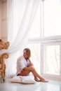 Charming girl sitting on windowsill portrait of in sweater and looking through window Royalty Free Stock Photo