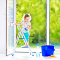 Charming girl washing a window cute laughing curly toddler big with squeegee in beautiful white living room with door into the Royalty Free Stock Photo