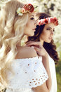 Charming girls in elegant dresses and flower s headband fashion outdoor photo of two beautiful posing blossom spring garden Royalty Free Stock Photo