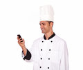 Charming guy in chef uniform texting on cellphone portrait of a while standing white background Royalty Free Stock Photos