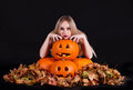 Charming halloween witch with funny pumpkins and leaves over black background Stock Photos