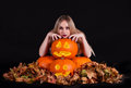 Charming halloween witch with glowing funny pumpkins and leaves over black background Stock Photo