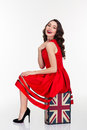 Charming happy woman posing on vintage suitcase with british flag young curly in red dress bright makeup in retro style Royalty Free Stock Photo