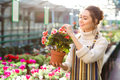 Charming happy young woman florist taking care of blooming begonia Royalty Free Stock Photo