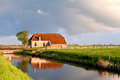Charming house by river in sunrise sunshine rainbow over Royalty Free Stock Photography