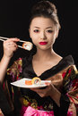 Charming Korean girl with dish sushi rolls Royalty Free Stock Photo