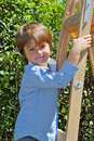 The charming little boy with a smile poses on step ladder in background spring green hedges Stock Image