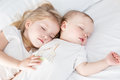 Charming little brother and sister asleep embracing on white background Royalty Free Stock Images