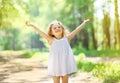Charming little girl enjoying summer sunny day raises his hands top happy child Stock Photos