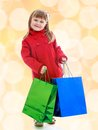 Charming little girl goes shopping with large multi colored packages Royalty Free Stock Photo