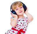 Charming little girl loves to listen to music through headphones isolated on white background Stock Photos