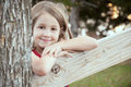 Charming lovely child portrait beautiful young girl leaning on fence post and smiling Royalty Free Stock Photo