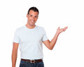 Charming man holding out his left palm portrait of a on white t shirt while standing and looking at you on isolated background Stock Photo