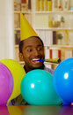 Charming man wearing blue shirt and hat sitting by table with balloons blowing party horn celebrating alone smiling Royalty Free Stock Photo