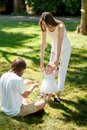 Charming mother and happy dad are teaching their little daughter wearing white dress how to make her first steps.