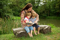 Charming mother reading a book to her adorable little twin sons while sitting outside near beautiful lake at summer Royalty Free Stock Photography
