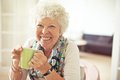 Charming old lady with a cup of tea closeup drinking her Royalty Free Stock Photography