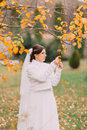 Charming pensive bride in autumn park looking to yellow leaves Royalty Free Stock Photo