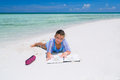 Charming pretty little girl, lying down on a sunny gorgeous beach and practicing how to draw in her sketch book