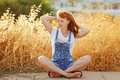 Charming red-haired girl in denim overalls sitting on a background of yellow dry grass at sunset in summer Royalty Free Stock Photo
